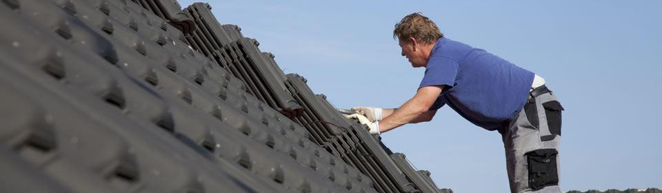 Dakdekker aan het werk met dakreparatie